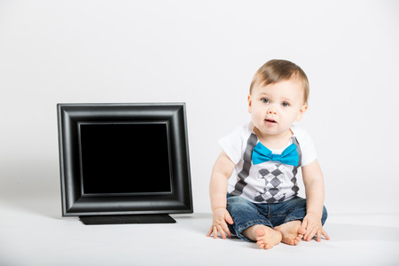 1 person: a cute 1 year old baby sits next to a blank black picture frame in a white studio setting. The boy is looking at the camera curiously. He is dressed in Tshirt, jeans, suspenders and blue bow tie
