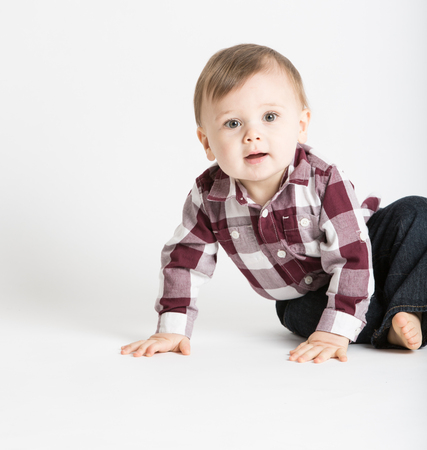 looking to camera: a cute 1 year old baby stands in white studio with jeans and a red white flannel looking camera left in excitement
