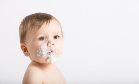 귀여운 1 세 흰색 스튜디오 설정에 앉아있다. 케이크와 설탕으로 가득 찬 얼굴로 아기의 닫습니다. 그는 단지 흰색 기저귀를 입고있다