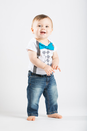 a cute 1 year old stands in a white studio setting. The boy has a happy expression. He is dressed in Tshirt, jeans, suspenders and blue bow tie Stock Photo