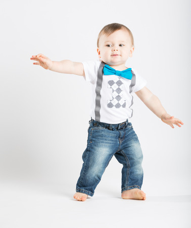 babies playing: a cute 1 year old stands in a white studio setting. The boy looks as if he is surfing in the studio.. He is dressed in Tshirt, jeans, suspenders and blue bow tie Stock Photo