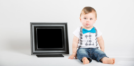 black blue: a cute 1 year old baby sits next to a blank black picture frame in a white studio setting. The boy has a confused expression. He is dressed in Tshirt, jeans, suspenders and blue bow tie