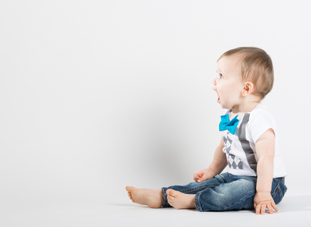 a cute 1 year old stands in a white studio setting. The boy is yelling with an open mouth. He is dressed in Tshirt, jeans, suspenders and blue bow tie 写真素材