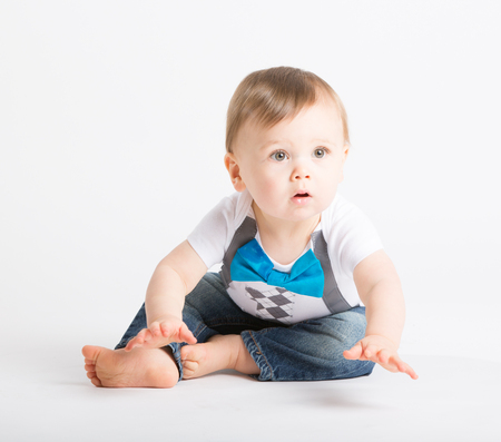 he old: a cute 1 year old sits in a white studio setting. The boy looks like he is about to start crawling. He is dressed in Tshirt, jeans, suspenders and blue bow tie