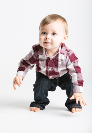 1 year old: a cute 1 year old baby stands in white studio with jeans and a red white flannel looking camera left in excitement