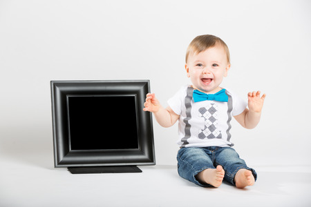 bebe sentado: una linda bebé de 1 año de edad se sienta junto a un cuadro negro en blanco en un entorno blanco del estudio. HBarra niño es extremadamente emocionados con las manos en el aire. Está vestido con camiseta, pantalones vaqueros, tirantes y corbata de lazo azul
