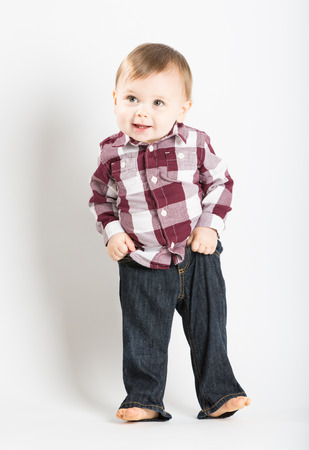 a cute 1 year old baby stands in white studio with jeans and a red white flannel looking camera left in excitement and pulling up his pants