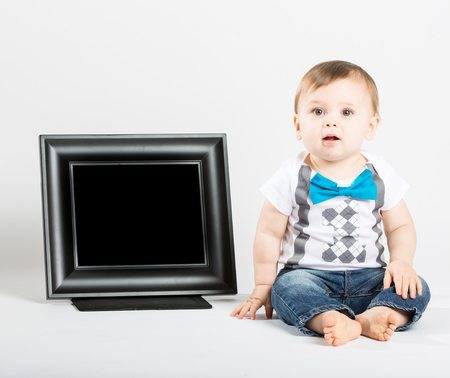 next year: a cute 1 year old baby sits next to a blank black picture frame in a white studio setting. The boy is sitting in inticipation. He is dressed in Tshirt, jeans, suspenders and blue bow tie