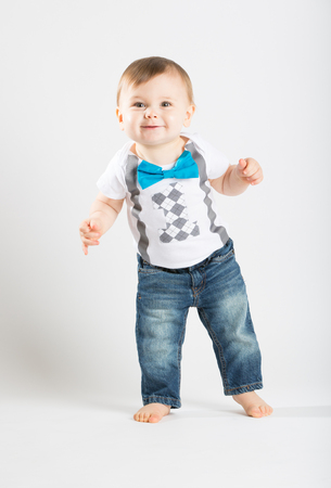 bare feet boys: a cute 1 year old stands in a white studio setting. The boy has a happy expression. He is dressed in Tshirt, jeans, suspenders and blue bow tie Stock Photo
