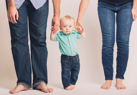 a 6 month old baby holding his parents hands looking at camera with eyes wide open