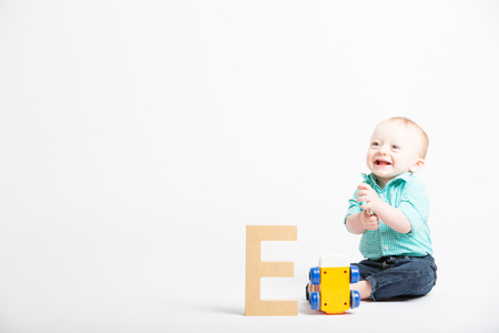 baby sit: a 6 month old baby sitting in a white studio looking off camera next to a toy and a wooden letter e Stock Photo