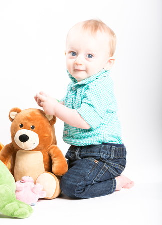 a boy kneels down next to stuffed animals and looks back at camera smiling