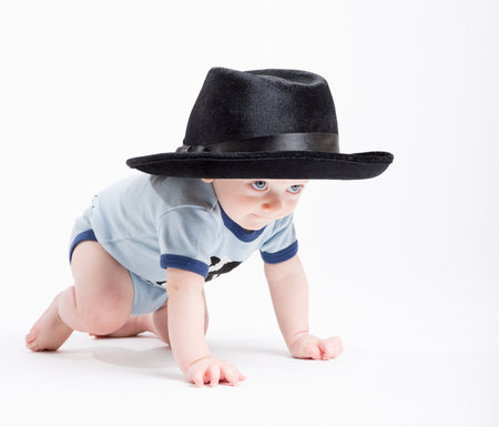 a 6 month old baby crawls on a white background wearing a black fedora hat