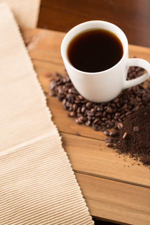 a coffee mug with coffee on a table with coffee beans and grounds on a wooden table with a cloth from above 写真素材