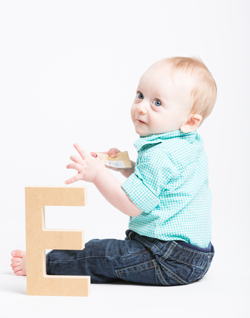 a 6 month old baby sitting in a white studio next to a wooden letter e