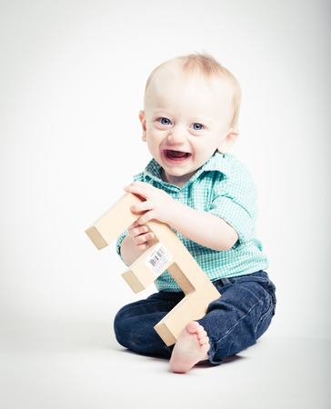 a 6 month old baby sitting in a white studio looking at camera smiling holding a wooden letter e