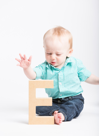 a 6 moth old baby reaches out to grab a wooden letter e
