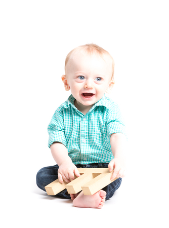 a 6 month old baby sitting in a white studio looking off camera