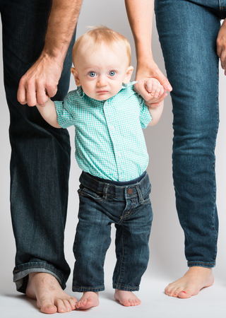 a 6 month old baby holding his parents hands looking at the camera