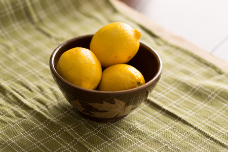 three lemons in a brown bowl sitting on a green cloth