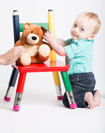 a boy is kneeling next to a chair with a teddy bear sitting on it. he looks back at camera Stock Photo