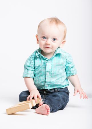 a 6 month old baby sitting in a white studio looking at camera