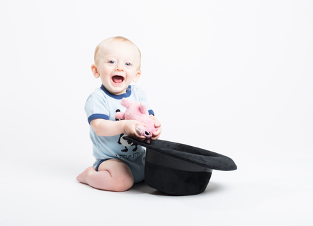 a 6 month old baby kneeling on white finds a stuffed animal pig is inside a black fedora hat and smiles at camera