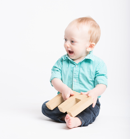 a 6 month old baby sitting in a white studio looking to the left holding a wooden letter e