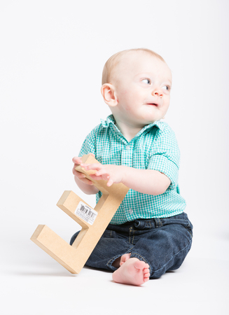 a 6 month old baby sitting in a white studio holding a wooden letter e looking off camera