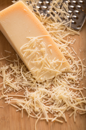 Parmesan Cheese and Grater Close Up. an angled view of a block wedge of parmesan cheese with shredded pieces all around and a metal cheese grater on a cutting board