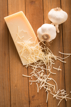 Garlic and Parmesan Cheese Shredded on Wood Board Above. an above shot looking down on a wedge of parmesan cheese and two cloves of garlic with shredded slices of cheese on top 写真素材