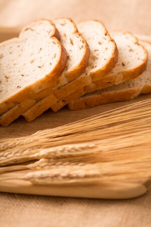Wheat Bread Slices on a Cutting Board with Wheat. a side angle shot of slices of wheat bread angled on a cutting board with wheat in the foreground 写真素材