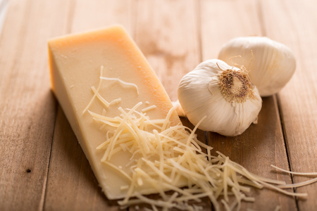 Parmesan and Garlic Close Up. an close up view of a wedge of parmesan cheese and two cloves of garlic on wood with shredded cheese 写真素材
