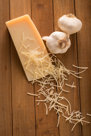 Shredded Parmesan and Wedge with Garlic Above. an above shot looking down on a wedge of parmesan cheese and two cloves of garlic with shredded slices of cheese on top 写真素材