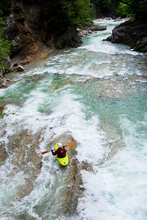 kayaker on the rapid of a turbulent river, the Alps, Austria photo
