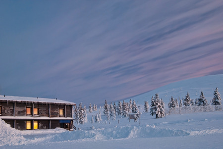 house covered with snow and sunrise. Finland, Lapland photo