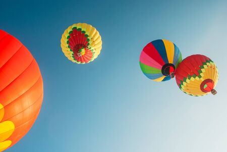 the view from below: soaring up colored balloons on a background of blue sky, view from below