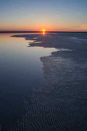 Sunset on a lake with a rugged coastline. Salt Lake Elton, Russia.