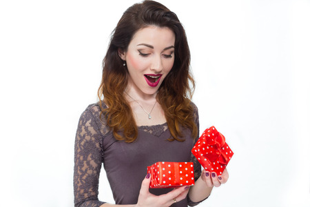 Happy cute woman opens a gift box