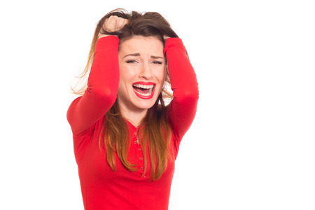beautiful crying woman: emotionally stressed woman in red grabbing her hair isolated