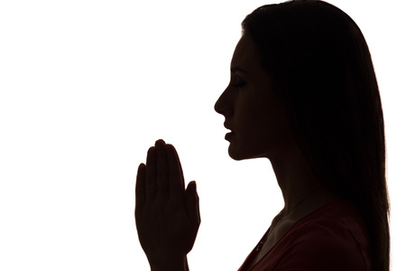 closeup profile of a woman praying in silhouette isolated