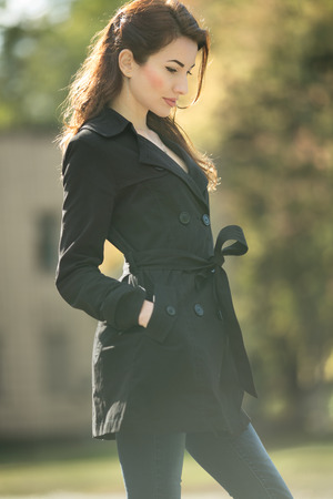 awesome vintage woman looking away in trench coat at fall time Stock Photo