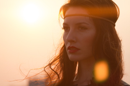 Portrait of a hippie woman with headband looking far away at sunset with windy hair. Shot with anamorphic flare. Vintage looking hippie girl looking at distance. Closeup
