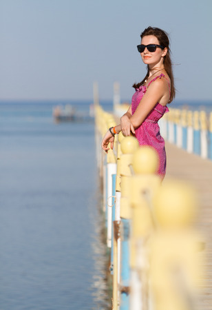 Pretty girl on vacation i standing at a pier enjoying sunshine. Woman in sunglasses is waiting for someone at the sea peer. Freedom and waiting concept
