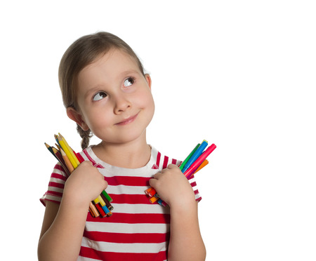 cute little girl holding colourful pencils and markers looking up imagining ideas isolated on white background