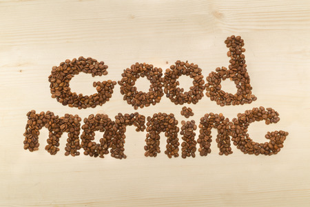 Phrase good morning made with coffee beans on a table top view close-up