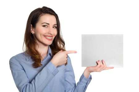 Positive smiling woman  in blue shirt pointing at blank piece of paper copy space isolated on white background Imagens