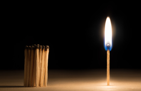Crowd of burnt  matches standing before match on fire concept of motivation leadership on black