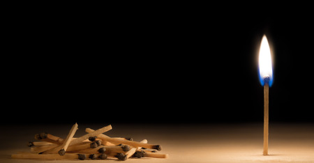 Pile of burnt matches laying down in front of one burnig match metaphor on black background