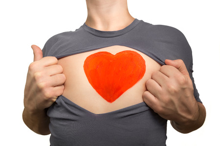 Man tearing apart grey t-shirt. Red heart painted on his chest isolated on white background